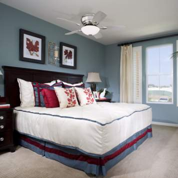 The blue, red, and white bedroom color scheme provides a relaxing aesthetic.