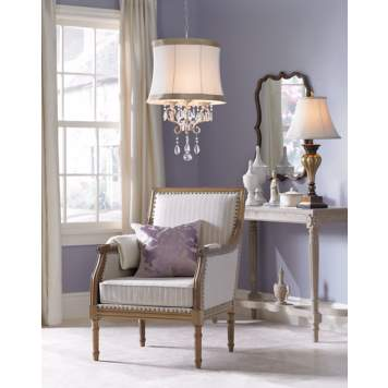 A shade chandelier brings sparkle and elegance to this bedroom seating area.