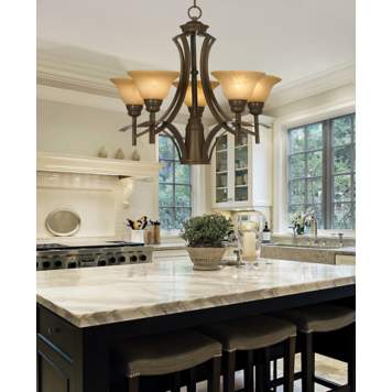 Mini pendant chandeliers cast an inviting glow in this traditional kitchen.