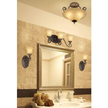 Bronze and gold light fixtures highlight this luxurious bathroom design.