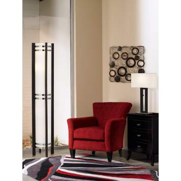 The wall art and black area rug defines the pattern in the living room picture.