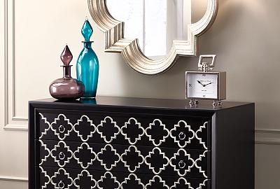 Combine an accent chest, wall sconce lighting, and mirror to brighten a hallway.