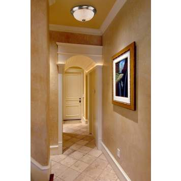 A subdued frosted glass ceiling fixture adds unobtrusive lighting to a hallway.