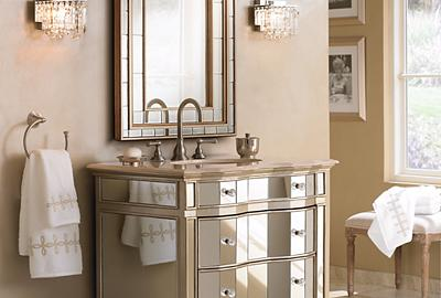 A glamorous bathroom with plenty of mirrors and mirrored furniture.