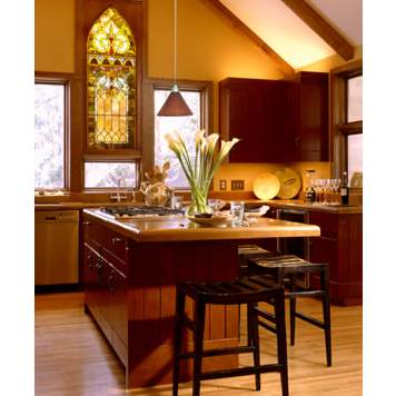 A stained glass window is a bold architectural accent in a transitional kitchen.