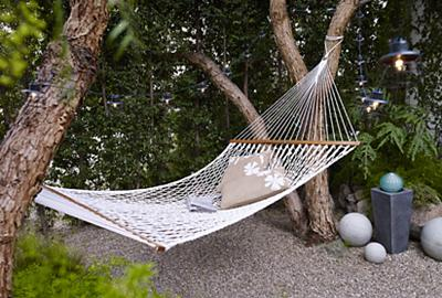 A simple and peaceful outdoor retreat with a large rope hammock.