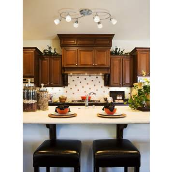 A curved track light adds modern style to a traditional kitchen picture.