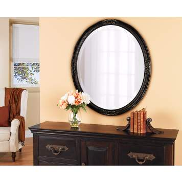 A large oval mirror brightens a traditional entryway.