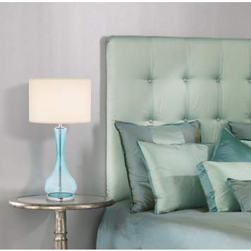 The light blue hues and glass table lamp define the contemporary bedroom.