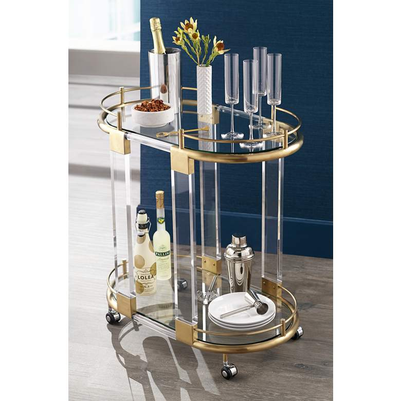 "Adaline 29 1/2"" Wide Clear Acrylic and Gold Oval Bar Cart in scene"