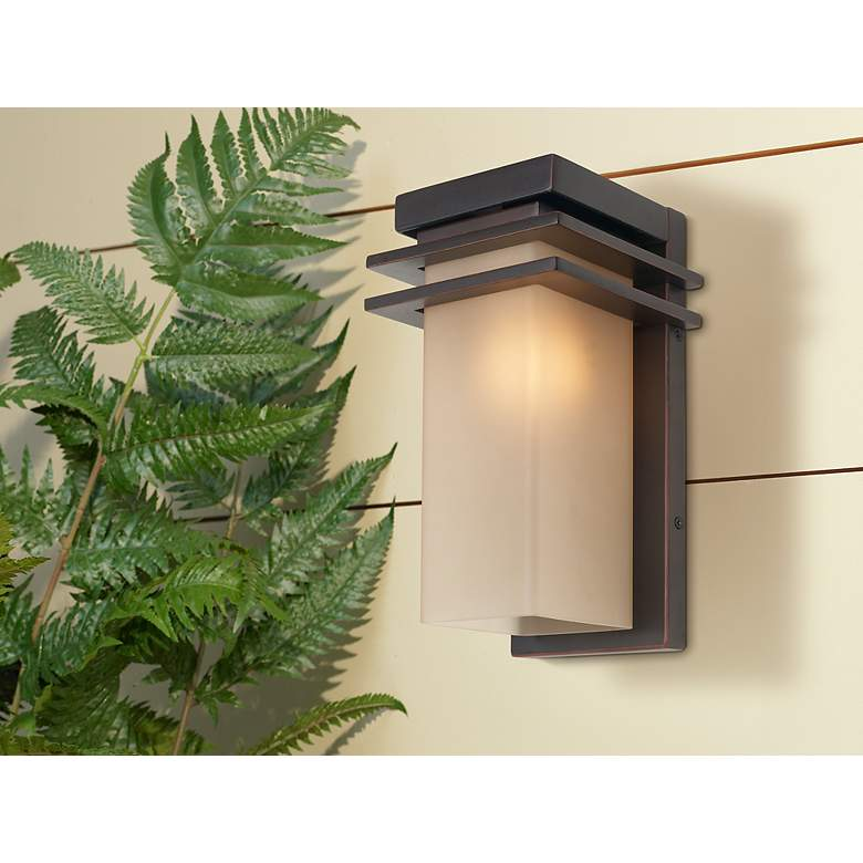 "Bernadine 12"" High Bronze and Amber Glass Outdoor Wall Light in scene"